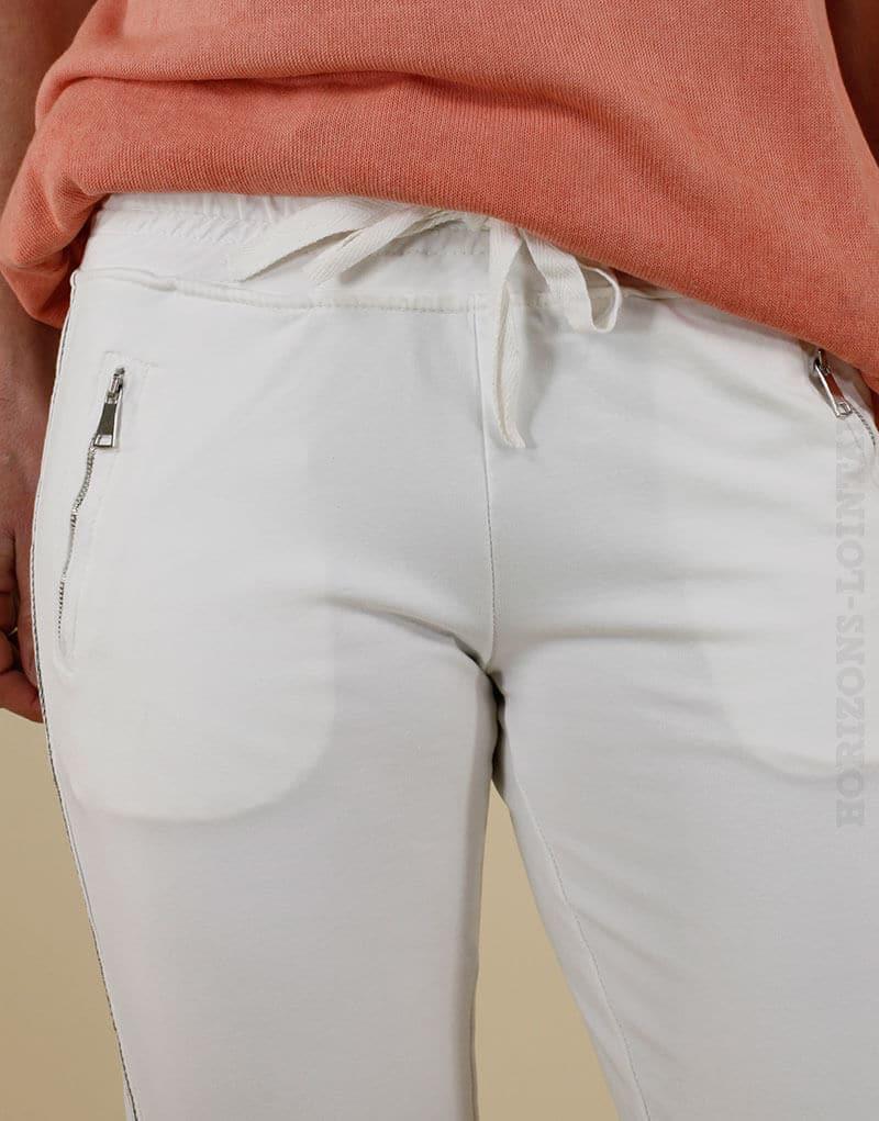 Jogging blanc avec un bande brillante sur le côté, poches zippées