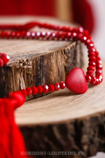 Collier rouge sautoir perles facettes trois petits cœurs effet craquelé pompons couleur